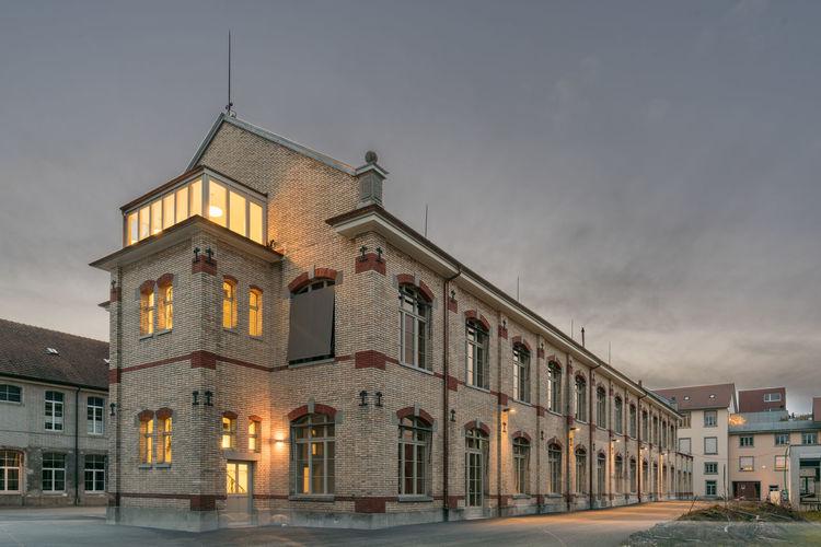 Illuminated building against cloudy sky at dusk