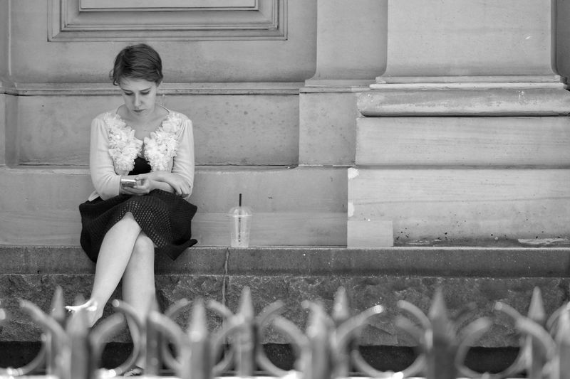 One Person Day Outdoors Sitting People Photography Monochrome Melbourne City Street Photography Black And White Real People City Street Life People Watching One Woman Only On The Phone Mobile Phone Only Women Young Women Women Seated Welcome To Black Plastic Cup Wall The City Light Spontaneous