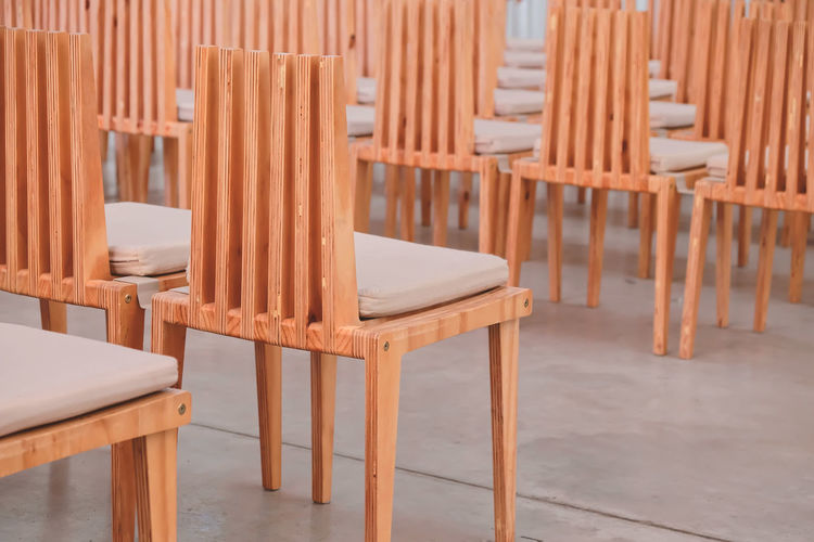 Wooden chairs in a row in a church. Wood - Material No People Brown Indoors  Arrangement Seat Chair Close-up Furniture Empty Wood Chair Modern Row Wooden Wood Church Conference Room Ferniture Interior Vintage