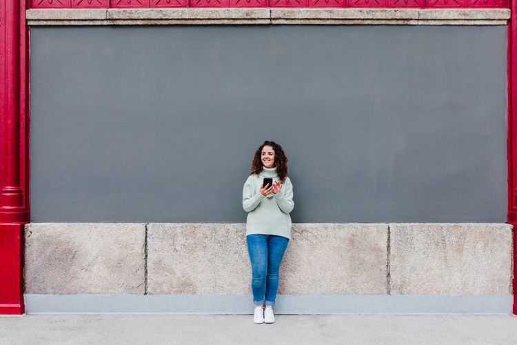 Full length portrait of young woman standing against wall