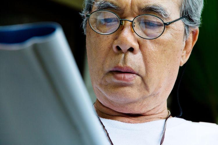 Close-up of senior man using digital tablet