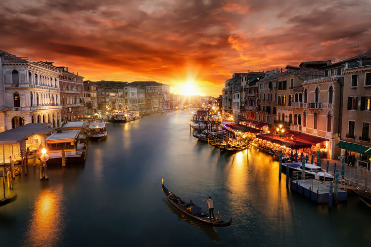 Sunset over the Grand Canal in Venice, Italy, on a summer evening Romantic Travel Architecture Attraction Bridge Canal City Cloud - Sky Destination Gondola - Traditional Boat Gondolier Illuminated Italy Nautical Vessel Reflection Sky Sun Sunlight Sunset Tourism Transportation Travel Destinations Venice Water Waterfront