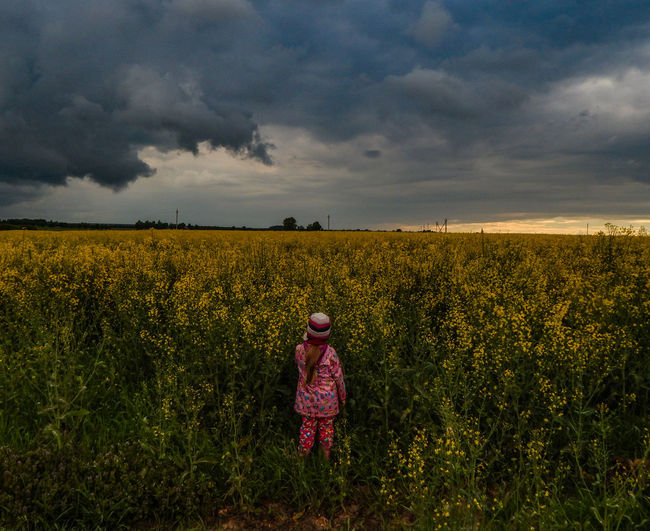 Rear view of girl standing at rape field against storm clouds