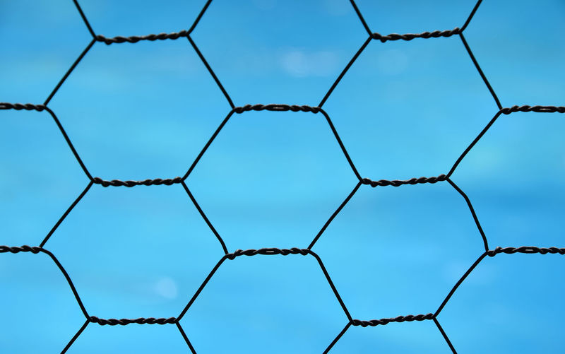 Full Frame Image Of Metallic Fence Against Blue Sky