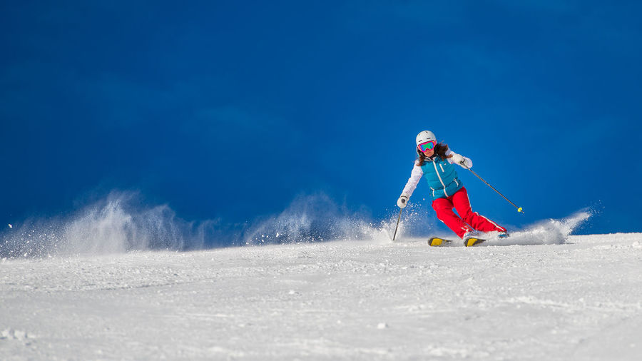 Full length of woman skiing on snow against sky