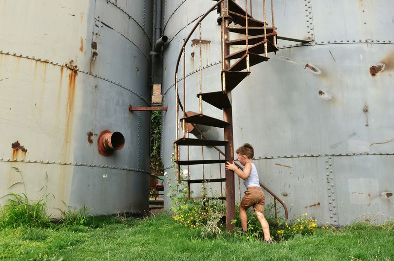 Full Length Of Boy Climbing Steps On Silo