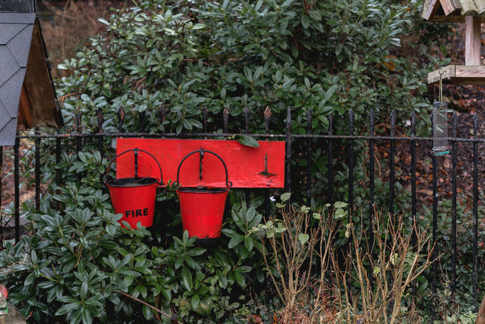 Fire buckets at a train station just out of Manchester, UK. Buckets Fire Buckets Railing Birdfeeder Bucket Day Fire Green Color Growth Ivy Leaf Metal Nature No People Outdoors Plant Plants And Flowers Railings Red Train Station Tree