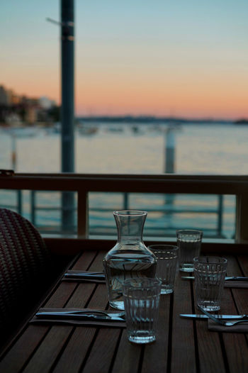 Table Sky Glass Chair Water No People Absence Drinking Glass Food And Drink Sunset Focus On Foreground Restaurant Place Setting Outdoors Household Equipment Nature Railing Empty Wood - Material Seat Setting Manly Beach Travel Photography Travel Destinations Travelling