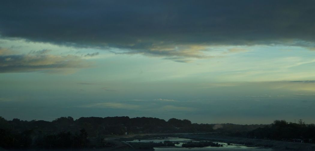 Storm clouds over landscape during sunset
