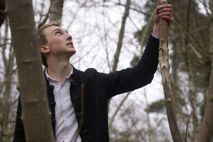Young man looking up while standing in forest