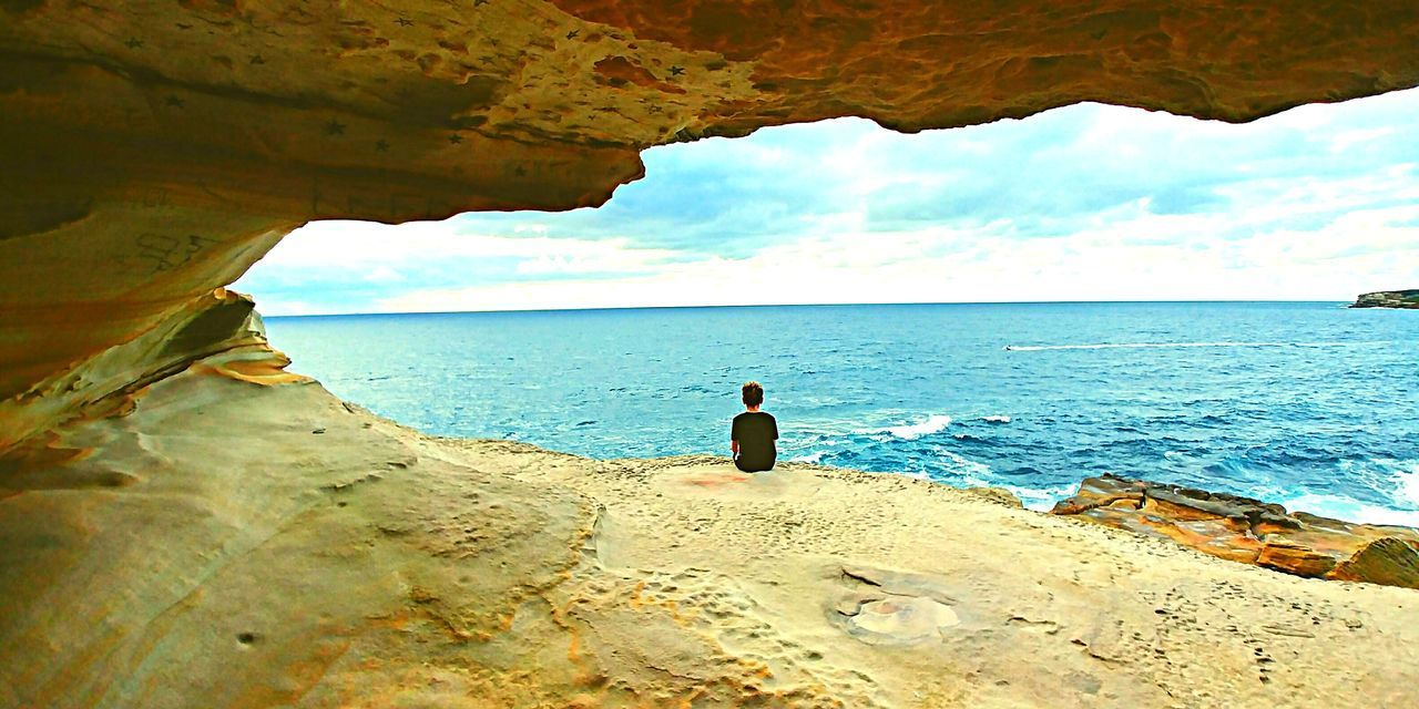 sea, water, one person, real people, leisure activity, lifestyles, beauty in nature, sky, land, rock, beach, horizon over water, scenics - nature, rock - object, tranquility, rear view, day, nature, outdoors, looking at view
