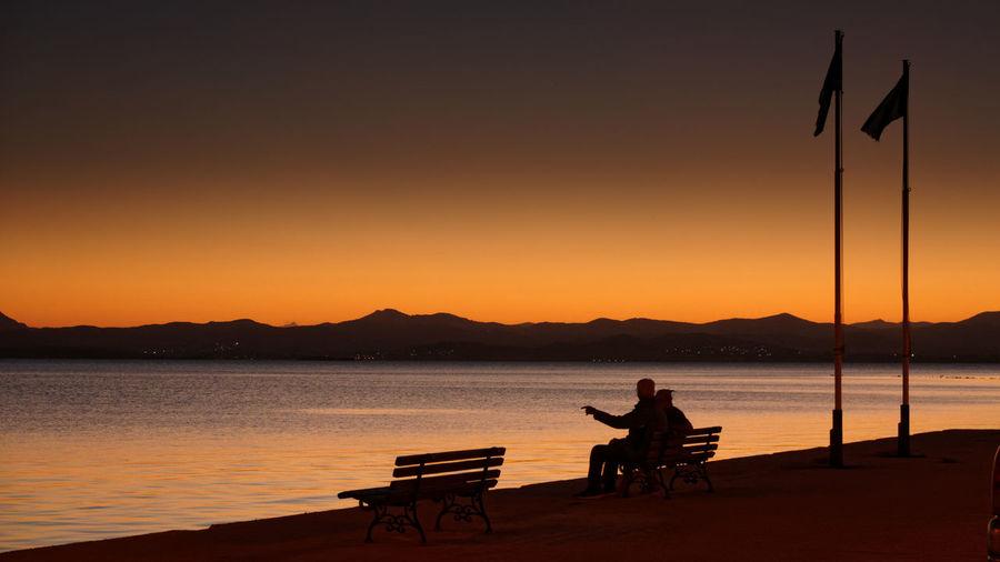 Silhouette man sitting by lake against orange sky