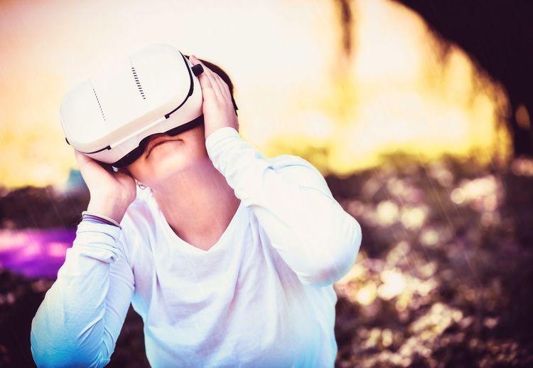 Close-up of boy using virtual reality headset at yard