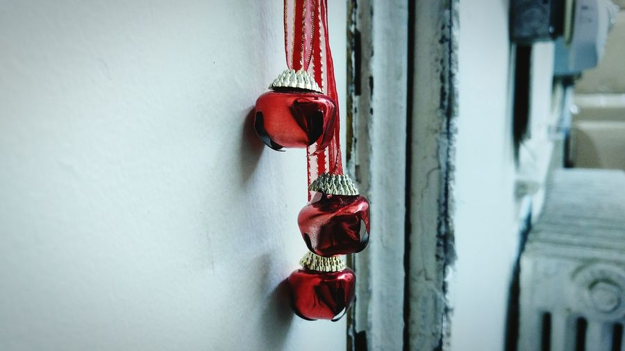 Close-up of red art decor hanging on white wall