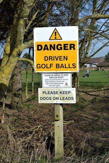 Danger - Driven Golf Balls, warning sign at the edge of the footpath across a golf course. Communication Sign Text Western Script Plant Tree Yellow Land Warning Sign Information Field No People Nature Information Sign Guidance Day Script Non-western Script Close-up Grass Warning Symbol Danger Golf Ball Driven Golf Balls The Art Of Street Photography