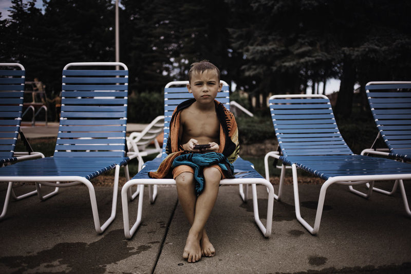 Portrait of boy sitting on lounge chair at poolside