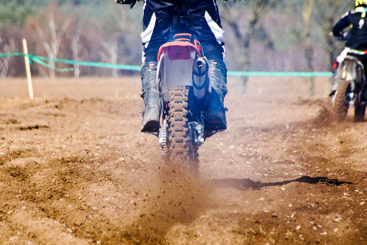 Low section of man riding motorcycle in motocross race on mud