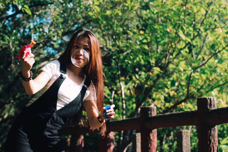 Portrait of smiling woman playing with bubble wand against trees