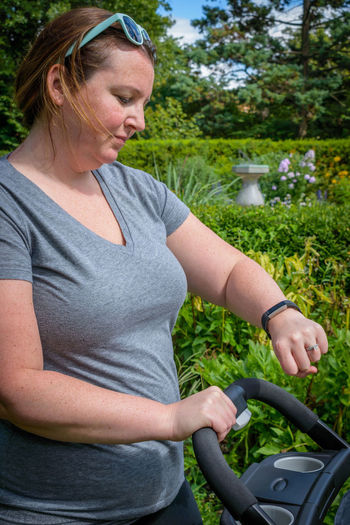 Woman looking at smart watch while holding baby stroller at park