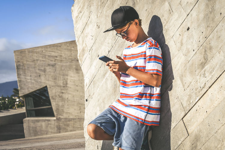 Boy using mobile phone while standing against wall