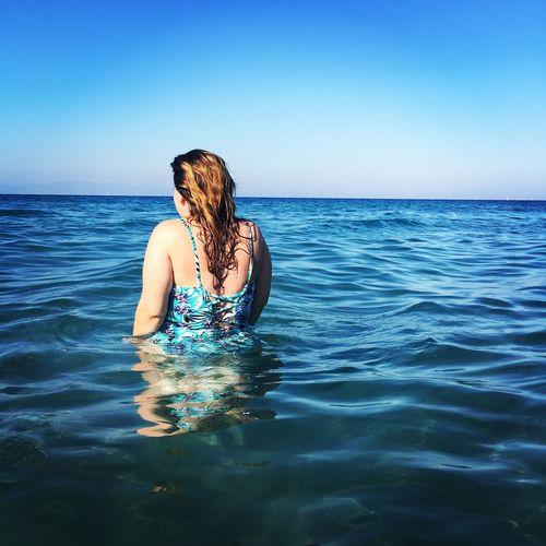 Rear view of woman wearing swimsuit in sea against blue sky