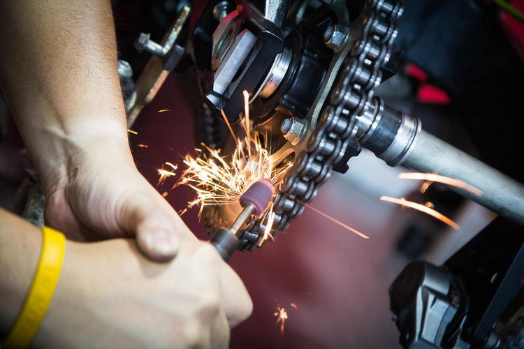 Cropped hands of mechanic repairing vehicle
