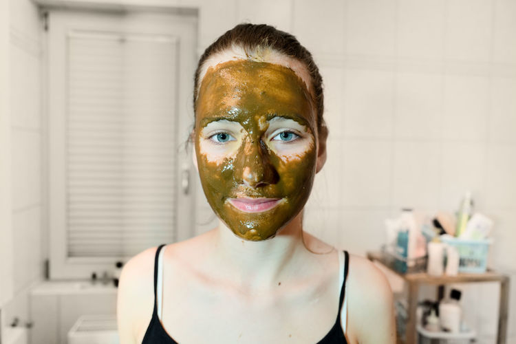 Portrait Of Young Woman With Facial Mask In Bathroom