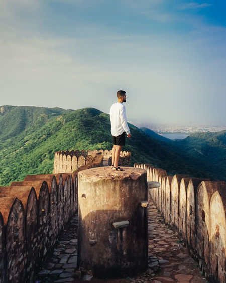 Side view of man standing on wall