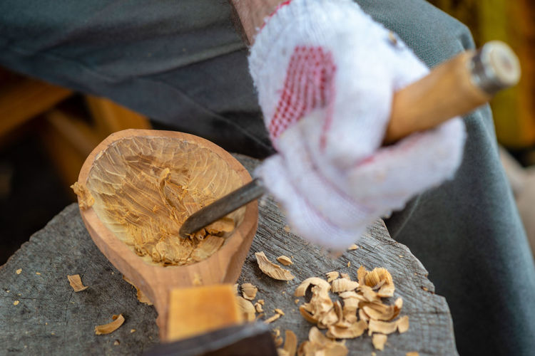 Craftsman demonstrates the process of making wooden spoons handmade using tools. National crafts concept. Carver Christmas Craftsman Hands Latvia Market Sale Xmas Carpenter Carpentry Carving Craft Craftsmanship  Creative Decorative Design Equipment Handmade Riga Spoons Tool Traditional Vintage Wooden Woodwork