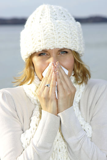 Woman with cold snuffs into a tissue Autumn Catched A Cold Tissue Walk Winter Woman Beautiful Woman Best Age Blond Hair Close-up Cold Cold Temperature Day Lake One Person Outdoors People Portrait Scarf Sick Snuffs Warm Clothing Winter Young Adult Young Women