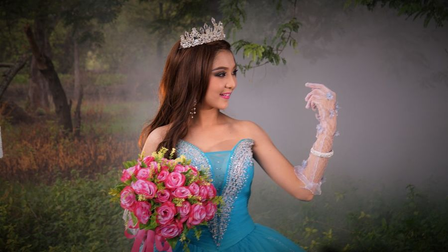 Beautiful woman in blue dress holding bouquet while standing on field at park
