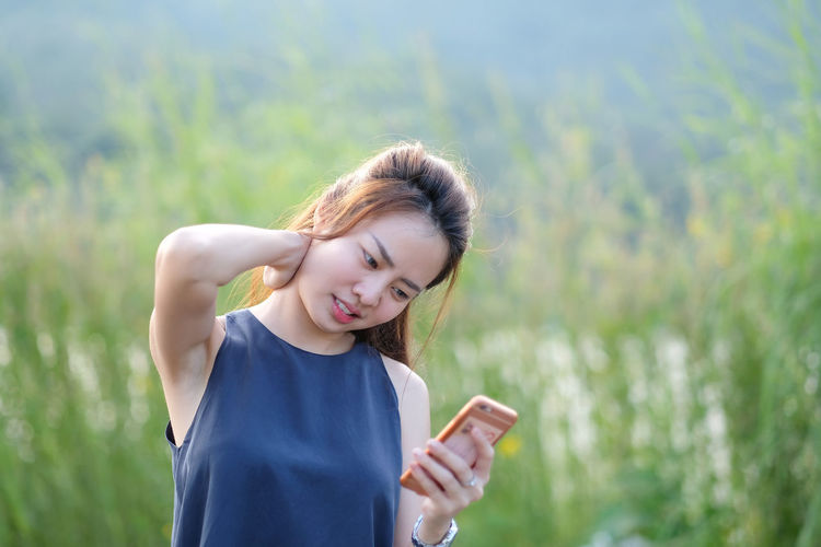 Woman Using Phone While Standing Against Plants