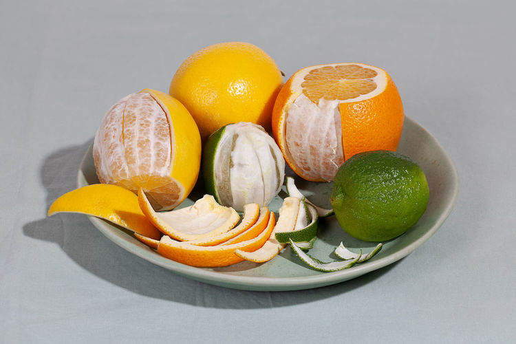 Close-up of fruits in plate against white background