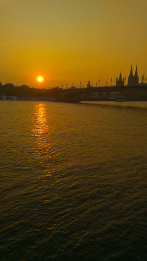 Sunset by river Rhine at Cologne Köln Rhein Architecture Beauty In Nature Building Exterior Built Structure Dom Cathedral Nature No People Orange Color Outdoors Scenics - Nature Sea Shillouette Sky Sun Sunset Tranquil Scene Tranquility Travel Travel Destinations Water Waterfront