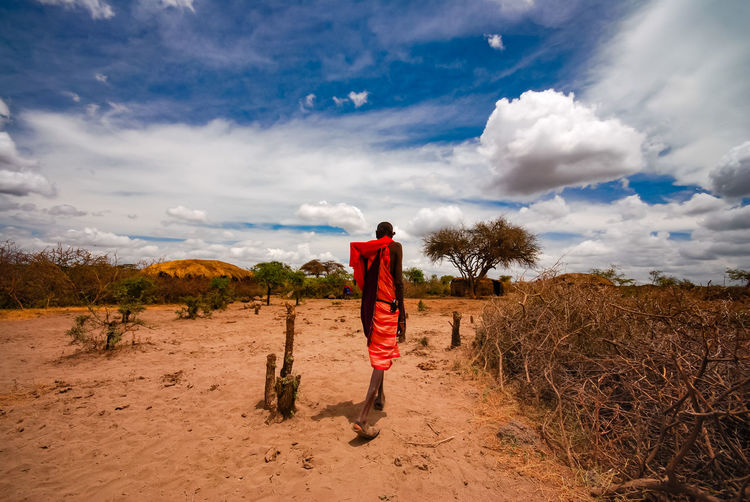 Rear view of man standing on field against sky masai village