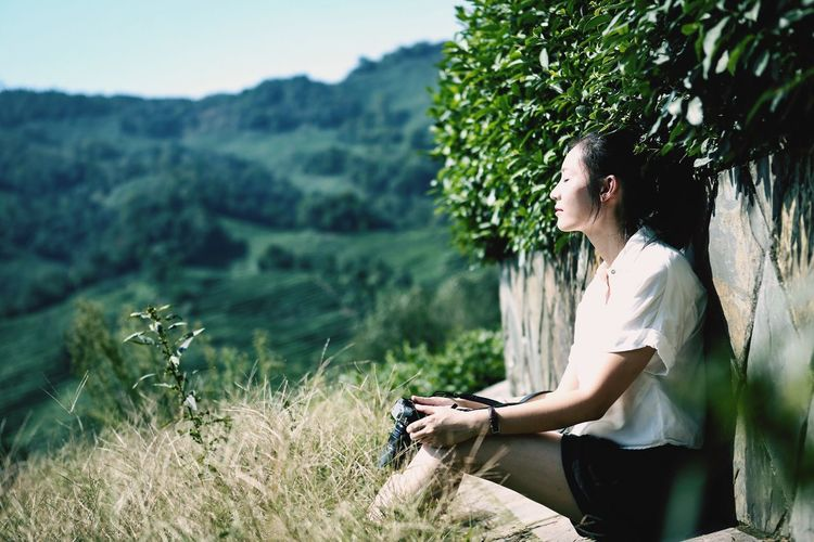Side view of woman sitting on by wall on mountain