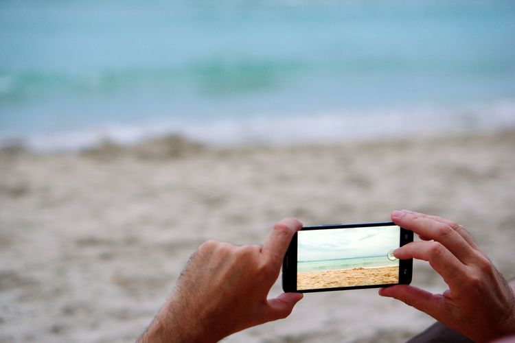 Cropped Image Of Man Photographing Sea At Beach On Mobile Phone