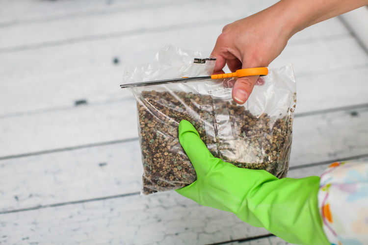 Cropped hands of person cutting bag with stones on table