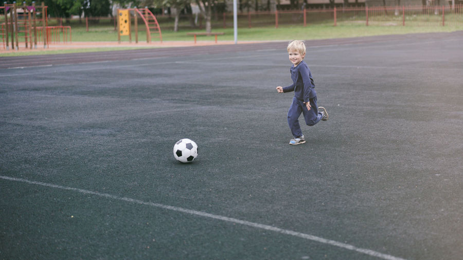 Full Length Of Boy Playing Soccer At Playground