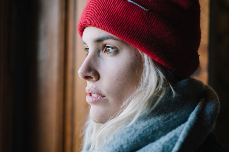 Thoughtful woman against wall in winter