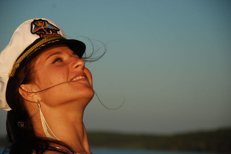 Close-up of woman wearing sailor hat looking up