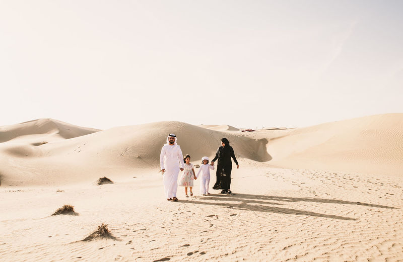 Happy family walking on sand dune