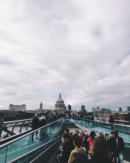 People At London Millennium Footbridge With St Paul Cathedral Against Cloudy Sky