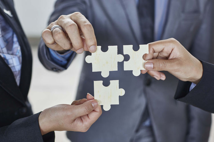 Midsection Of Businessman With Colleagues Holding Jigsaw Pieces At Office