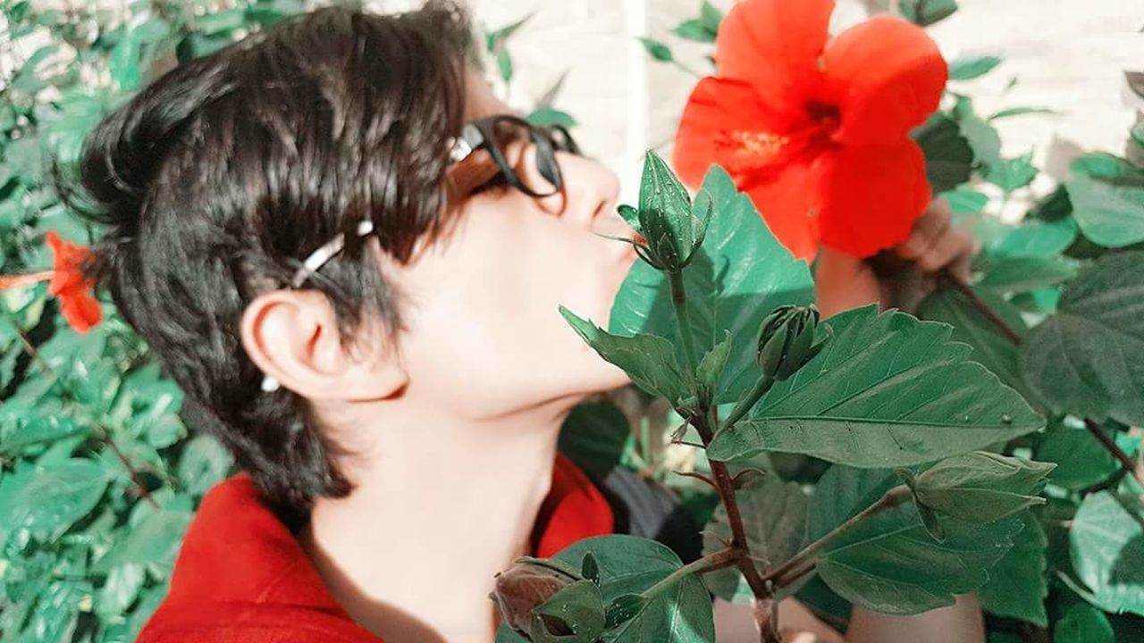 flower, leaf, child, plant, one person, childhood, fragility, growth, girls, nature, rose - flower, red, green color, human body part, outdoors, women, one girl only, close-up, children only, lifestyles, beauty in nature, day, flower head, people, real people, adult, freshness, greenhouse, human hand