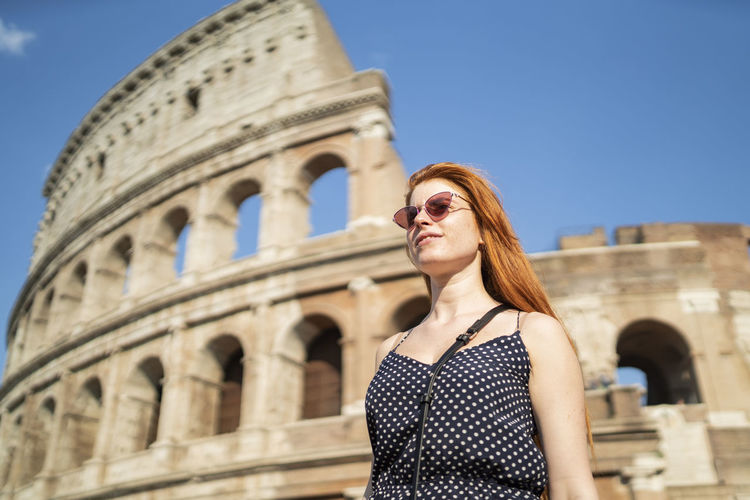 Portrait of beautiful woman standing against historic building