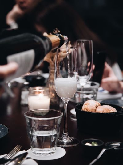 Close-up of bottle pouring champagne in flute on table