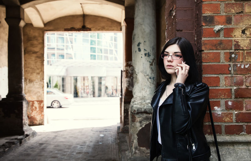 Sad young girl in black jacket and jeans stands in old arch on city street on summer day