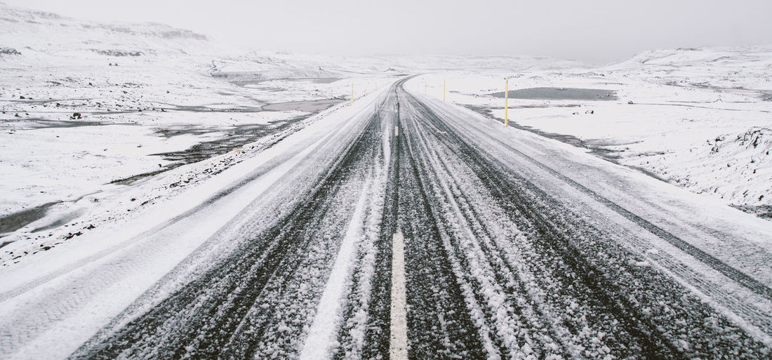 Snow covered road amidst landscape against sky