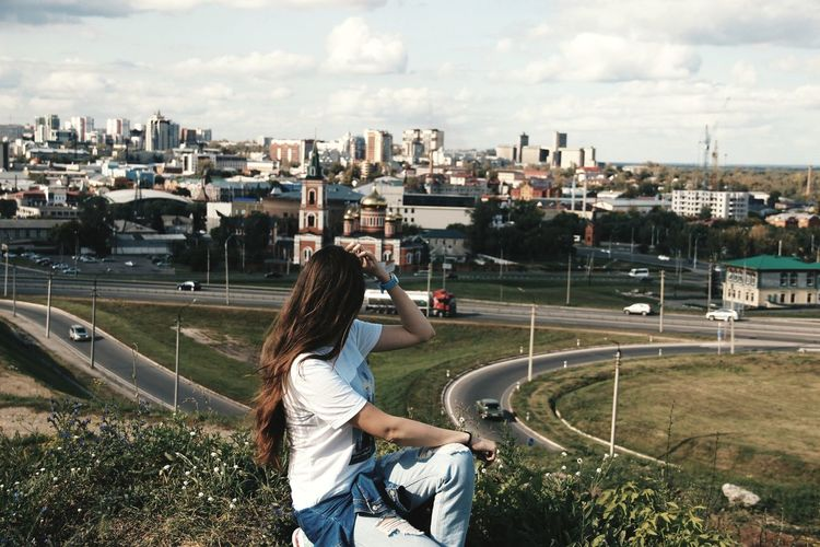 Side view of woman sitting on field against cityscape